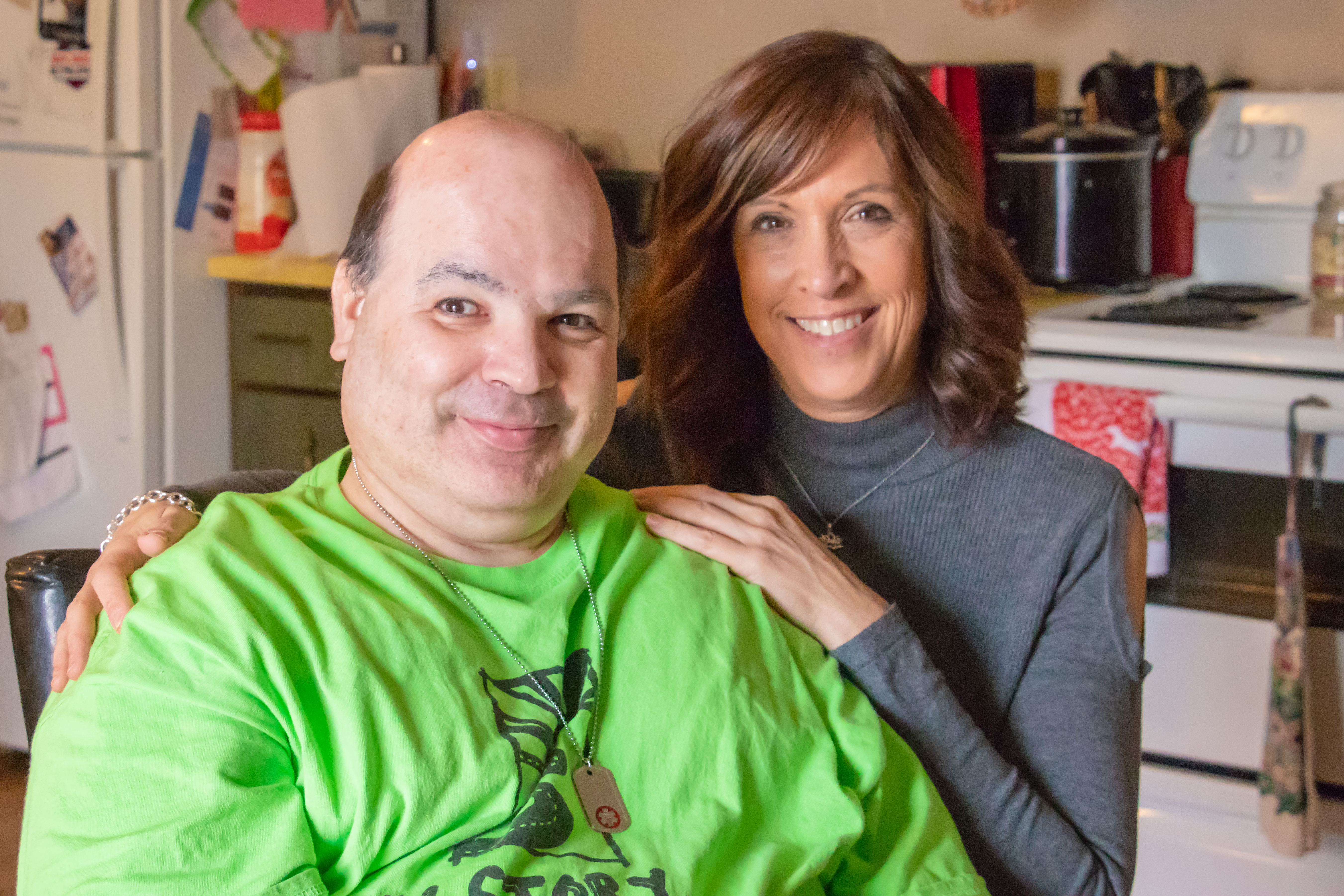 Man sits in his kitchen with a woman who is his service and support administrator