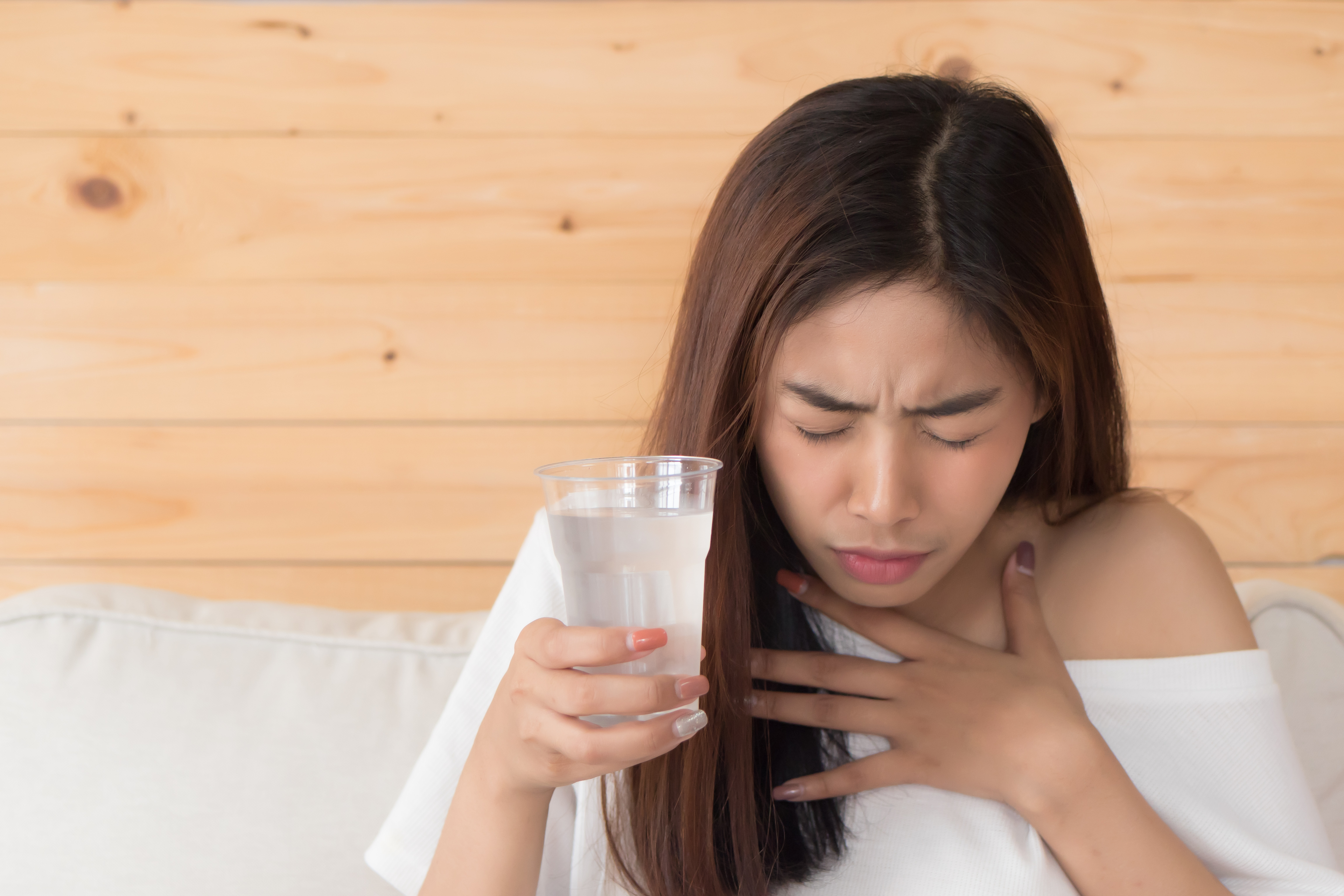 Woman choking from glass of water
