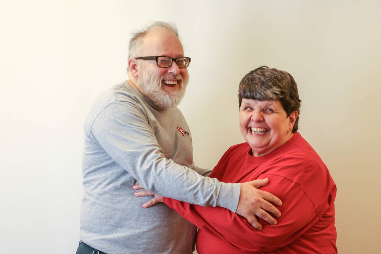 A middle age couple stands laughing with their arms around each other.