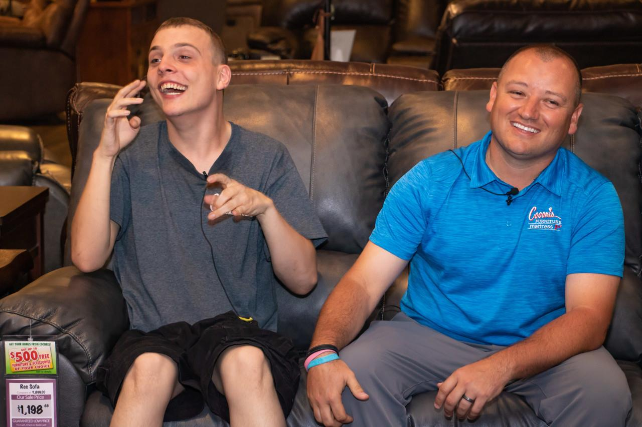 Two young men are sitting on a couch laughing.